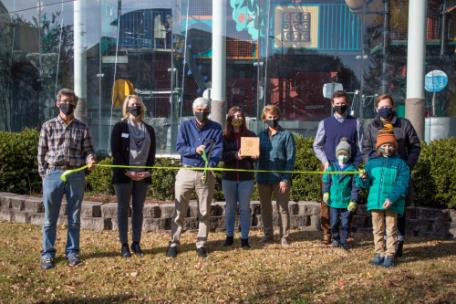 From left, Duane Rousseau, Katie Hanners, Henry Schulson, Ashley Bosecker, and Karen Dewhirst, of the Creative Discovery Museum celebrate the green|light ribbon cutting with green|spaces' Michael Walton, Kelley Cureton, and Finn and Henry Walton