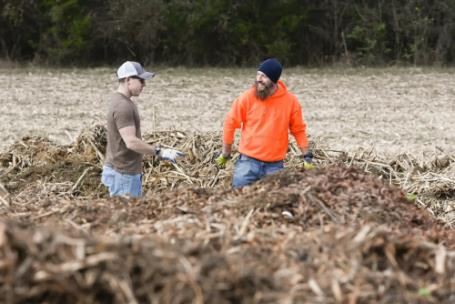Normand Lavoie, left, and his partner Michael Ryan stand in one the piles of compost they're creating at a site in Wildwood, Ga.