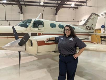 GNTC student Theresa Harper stands next to a plane in the GNTC Aviation Training Center hangar. Ms. Harper is the recipient of the HAI/WAI Maintenance Technician Certificate Scholarship and will receive recognition at the 32nd Annual International Women in Aviation Conference in March.