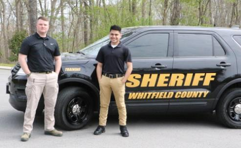 New recruits Micheal McClure (left) and Edgar Corona stand next to a Whitfield County Sheriff's Office vehicle the day before leaving for mandate training in Forsyth