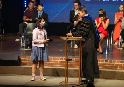 Lee President Dr. Mark Walker, right, presents Grace Ann Cochrane the Zeno C. Tharp Award during a special Honors Chapel
